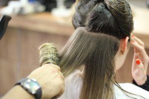 kobieta podczasz układania fryzury przez fryzjera