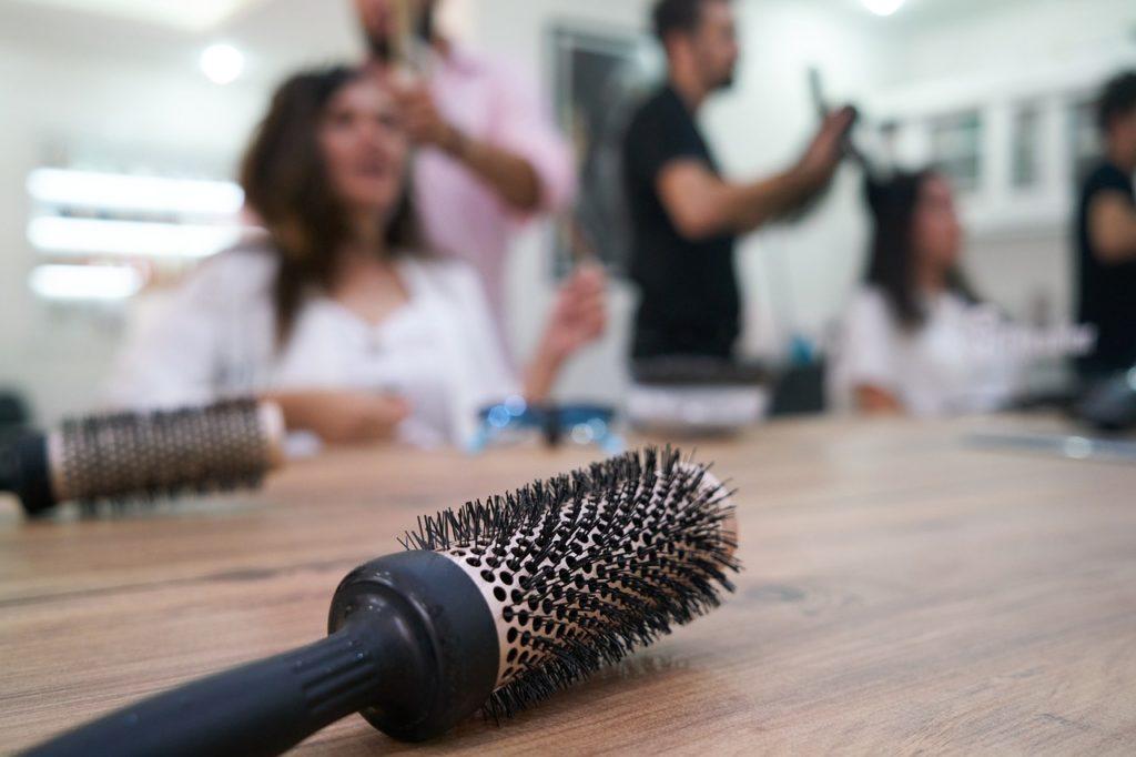 szczotka do włosów na stole, w tle klienci salonu fryzjerskiego